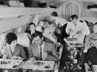 An Airline Steward and Air Hostess Serve a Roast Meal to Flight