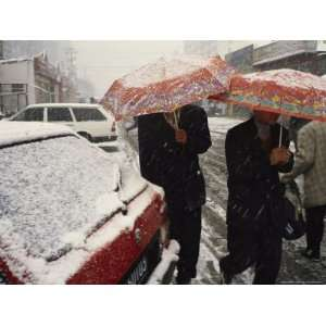 Muslim Uygur People Walk Through the Snow under Umbrellas